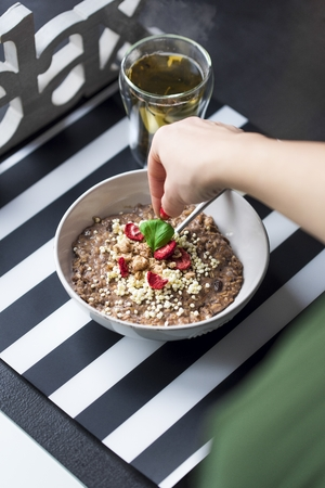 Breakfast with chocolate oatmeal prepared by a woman, puffed rice, cereals, dried strawberries in white bowl and green tea