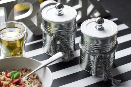 Metal containers for coffee and sugar stylishly decorated in Shabby chick style next to oatmeal and green tea Stock Photo