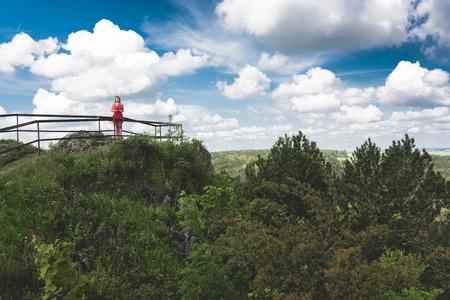 Mädchen im roten Kleid stand auf dem Rand der Klippe. Alte befestigte Siedlung am Kalkstein Berg Birmingham, Polen