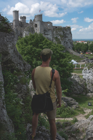 Man standing on the limestone cliff and looks at the castle in the distance, Poland