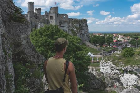 Mann steht auf der Kalksteinklippe und schaut auf die Burg in der Ferne, Polen