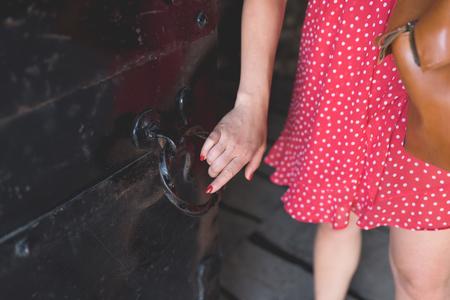 Mädchen im roten Kleid wird ein altes Tor öffnen, Ogrodzieniec Schloss Polen Lizenzfreie Bilder
