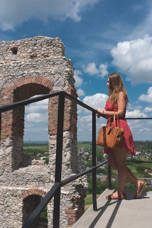 Fotografie von Ruinen Ogrodzieniec Schloss mit Mädchen im roten Kleid Lizenzfreie Bilder