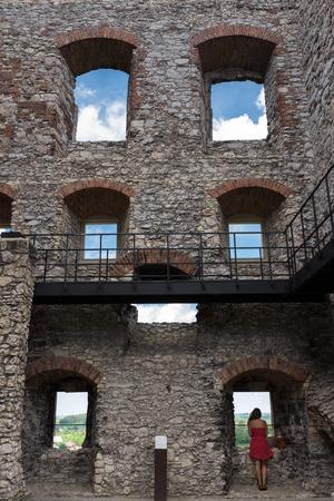 Fotografie von Ruinen Ogrodzieniec Schloss mit einem Mädchen im roten Kleid Blick durch das Fenster Lizenzfreie Bilder
