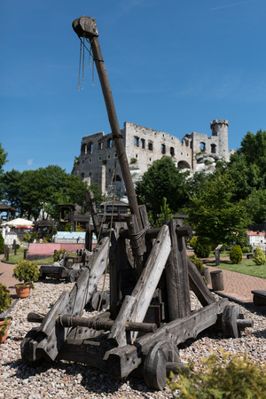 Medieval catapult made entirely of wood, Old castle Ogrodzieniec in the background