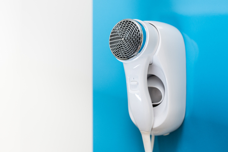 An electric hair dryer attached to a wall on a blue background Standard-Bild