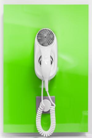Ein elektrischer Fön an einer Wand befestigt