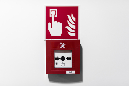 Red fire alarm button on white wall Standard-Bild