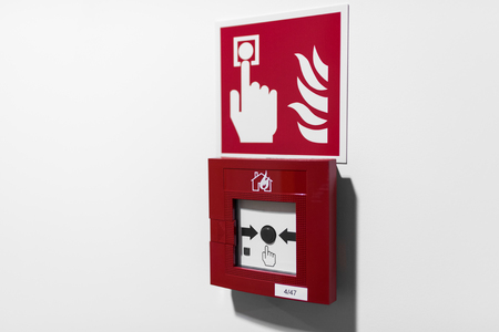 Red fire alarm button on white wall Stockfoto
