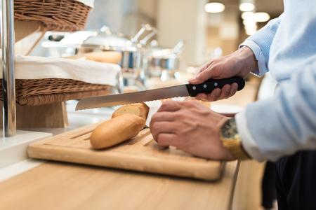 Geschäftsmann mit einer goldenen Uhr auf seiner Hand Schneide Baguette für sein Frühstück