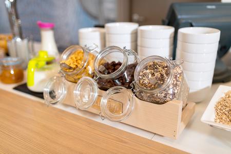 Frühstück im Hotel, Verpflegungsbuffet. Glas mit Museli, Cornflakes und Hafer.