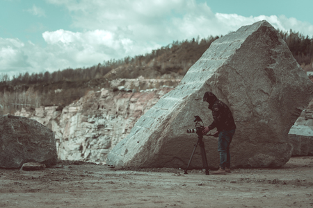 Video camera operator working on his quarry during daytime. Standard-Bild
