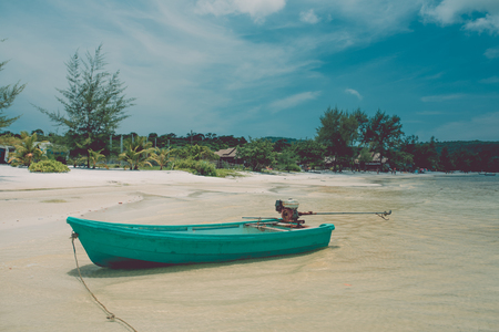 Turquoise motor boat on the beach. Beautiful weather with blue sky. Koh Rong Samloem island, Cambodia
