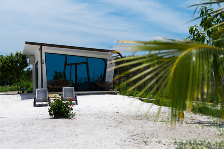 Beautiful white modern concrete bungalow with blue mirrored windows on the tropical island beach have been handed for use in september 2017. Koh Rong Island, Cambodia Asia.