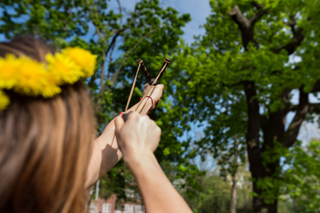 Girl shooting from the professional wooden slingshot in the park during a sunny day Stock Photo