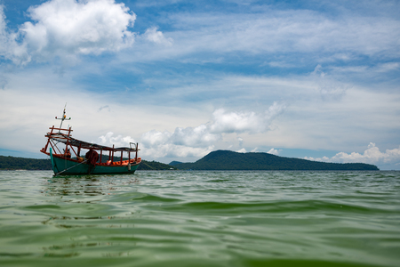 Green Longtail boat moored in Saracen Bay in Koh Ron Samloem, Cambodia. Beautiful clouds on the background.