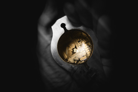 Golden Bitcoin lies on man hand under loupe. Hes checking if there was a fraud.