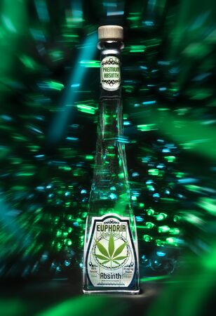 Bottle of Absinth Euphoria with cannabis standing on the green background. Product of Czech Republic. Nov 22, 2016 Wroclaw City. Poland.