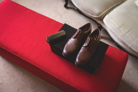 Casual brown leather male shoes placed on a cardboard box