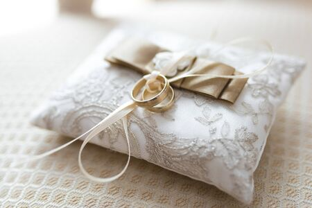 Golden wedding rings lies on a small decorated pillow 写真素材