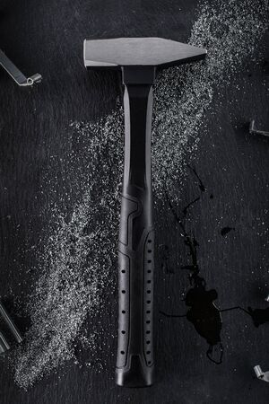 Black hammer made of reinforced steel placed on a black stone background. 写真素材