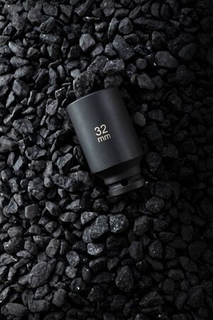 Black matt hex wrench head placed on a stony ground. 写真素材