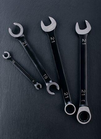 Professionelle verstärkte Open-End- und Schraubenschlüssel-Werkzeuge auf dunklem Hintergrund. Ausblick von Oben.