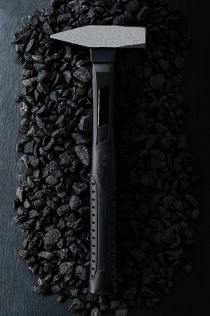 Professional reinforced black matt locksmith hammer placed on a stony background. View from the top.