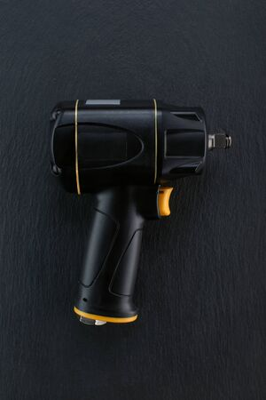 Professional Impact Air compressed wrench gun placed on a dark ground.