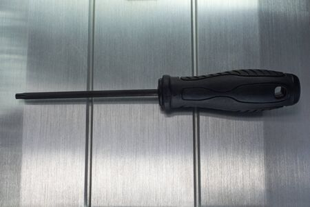 Professional reinforced black matt screw driver placed on a polished aluminum surface. View from the top.