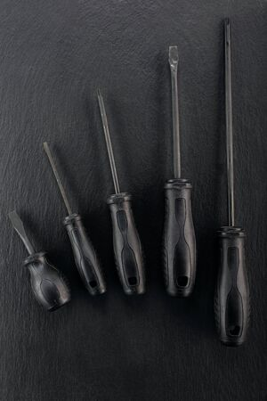 Professional reinforced black matt screw drivers placed on a dark ground. View from the top.