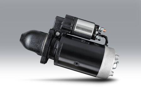 3-kW-Startermotor für Traktor oder andere Landmaschinen auf grauem, isoliertem Hintergrund mit Schatten. Standard-Bild