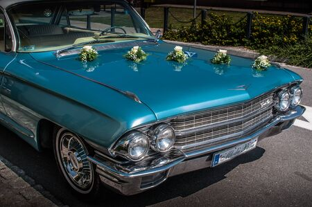 Front mask of 1962 CADILLAC DEVILLE sedan as a wedding car, standing on the street. Beautiful blue sky color. 02 august 2014 Wroc?aw, Poland.