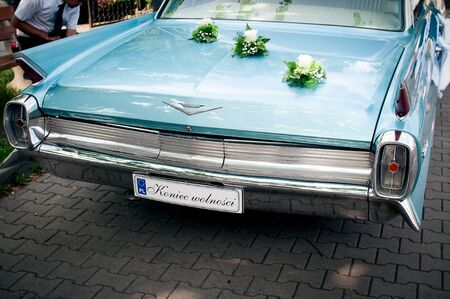 Back of 1962 CADILLAC DEVILLE sedan as a wedding car, standing on the street. Beautiful blue sky color. 02 august 2014 Wroc?aw, Poland.