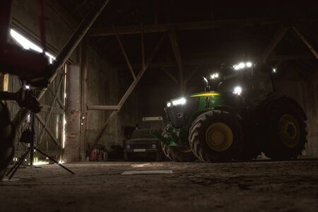 John Deere modern tractor parked in barn ready to drive outside for the field. April 6 2017 Wroclaw, Poland. Redakční