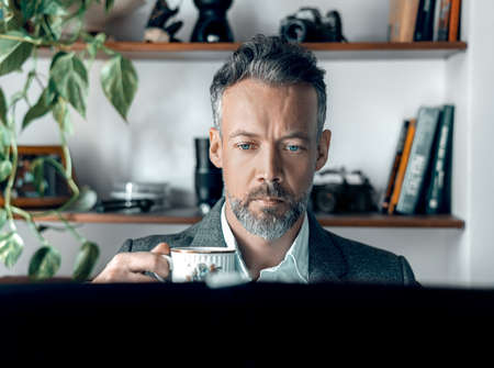 Handsome Man With Cup Of Coffee working on the Laptop At Home