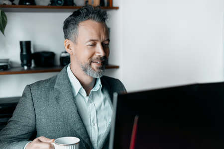 Happy Man With Cup Of Coffee working on the Laptop At Home Zdjęcie Seryjne