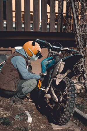 Emoji motocross rider with fancy black nerd sunglasses, preparing his motorcycle for a race before season. Emoji with mask protecting against coronavirus Covid 19. 3D rendering and photography collage