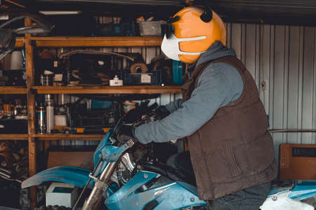 Emoji motocross rider with fancy black nerd sunglasses on his motorcycle inside of garage. Emoji with mask protecting against coronavirus Covid 19. 3D rendering and photography collage.