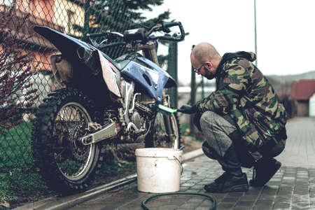 Young man washes motocross by hand, using a brush and hosepipe preparing motorcycle for race