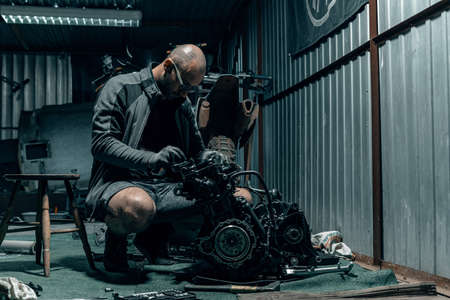 Young man repairing his motorcycle engine in the garage. The motorcycle engine is disassembled. Motor capital repair. Sixteen valves and four cylinder.