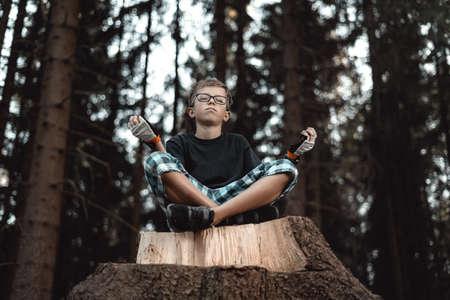 Teenage boy sitting on the tree stump and meditates
