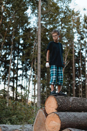 Teenager standing on the wood pile with forest in the background.