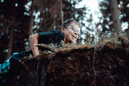 Portrait of happy Young teenager boy playing In the forest