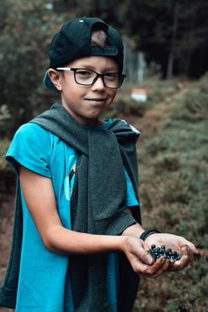 Young teenager boy standing in the forest with hands full of fresh ripe blueberries.