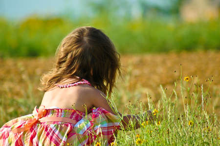 A little girl playing with flowers in a field