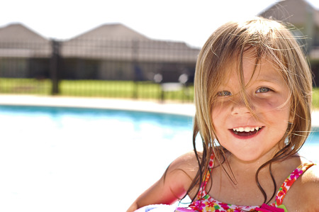 A little girl smiling in front of a swimming pool Stock Photo