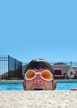 Boy with goggles at the swimming pool