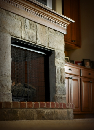 Stone and brick fireplace with wooden mantel photo
