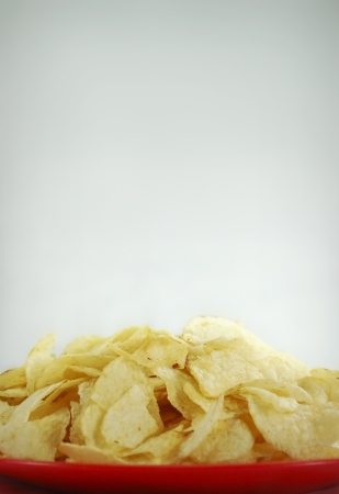 A bowl of greasy potato chips piled high
